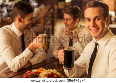 Three young businessmen in white classic shirts are talking, smiling and drinking beer while sitting in pub, blond man is looking at camera - stock photo