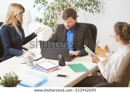 Three young businesspeople during business conference - stock photo