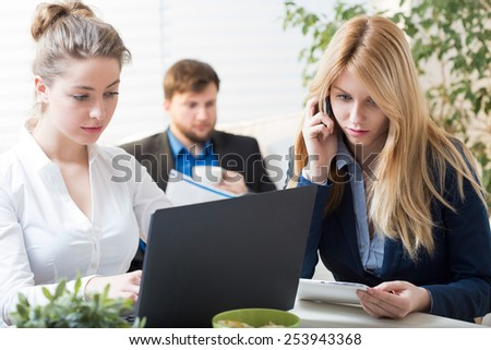 Three young busy businesspeople working together at the office - stock photo