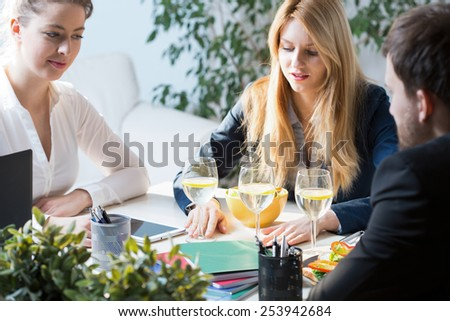Three young busy people on business lunch