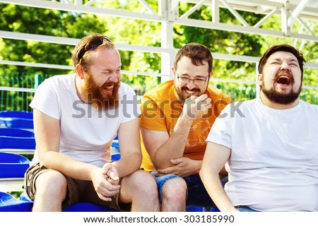 Three young cheerful friends are talking and laughing at summer day stadium background. - stock photo