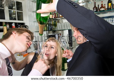 three young, drunken adults taking the last drop of champagne at a bar - stock photo