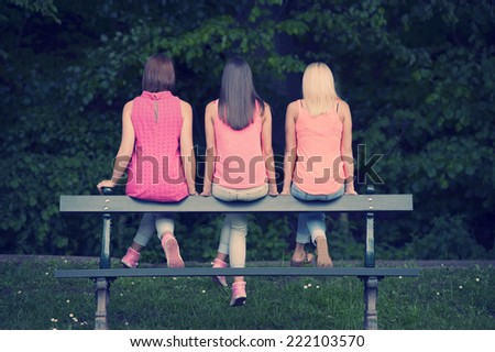 three young female friends seated on a bench, outdoors in the parc - stock photo
