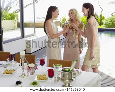 Three young female friends toasting champagne flutes at dinner party - stock photo