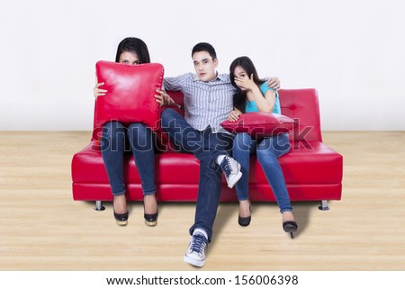 Three young friends are watching TV with fear at home