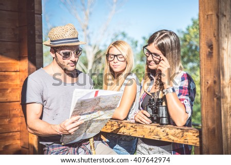 Three young friends looking at map and planning their summer holiday - Hikers consulting a map in a campsite - stock photo