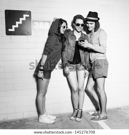 Three young friends looking at the pictures on the phone. Lifestyle - stock photo