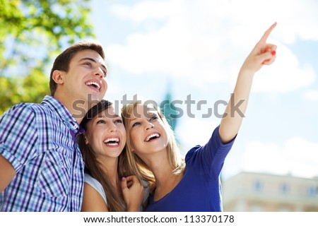Three young friends pointing - stock photo