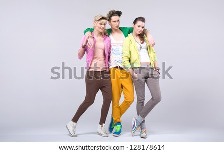 Three young friends posing on gray background