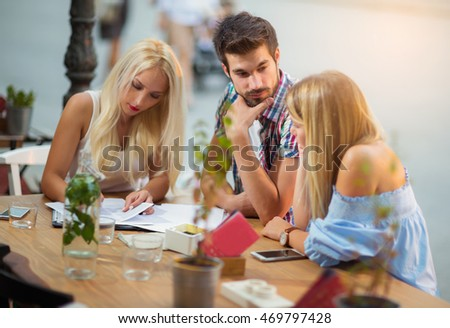Three young friends sitting in a cafe in front of them are miscellaneous papers to be completed
