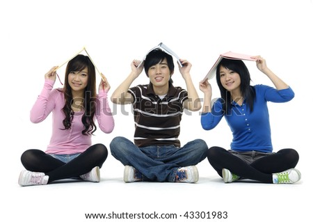 three young friends smiling with book on his head