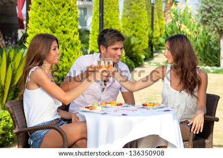 Three young friends, two women and a man, toasting while having lunch outdoors - stock photo