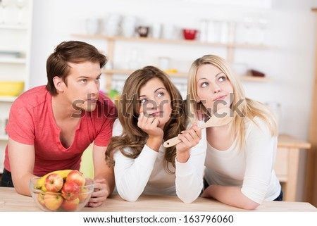 Three young friends undecided on what to cook leaning on a wooden counter in the kitchen staring pensively up into the air for inspiration - stock photo