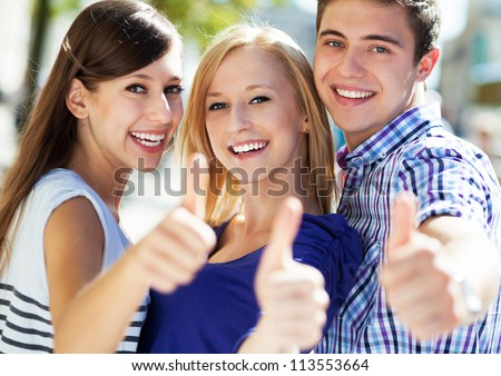 Three young friends with thumbs up - stock photo