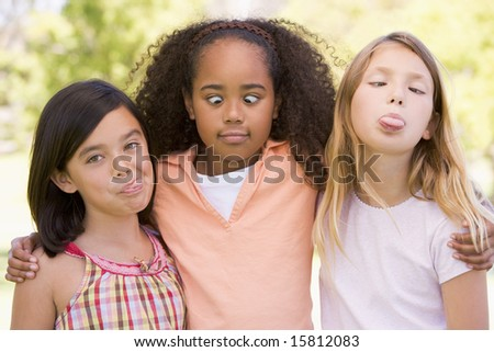 Three young girl friends outdoors making funny faces - stock photo