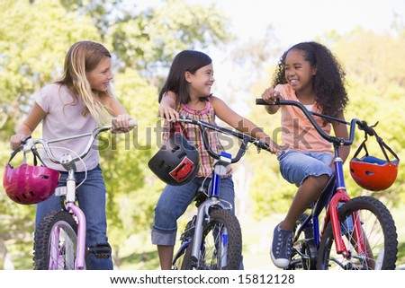Three young girl friends outdoors on bicycles smiling - stock photo