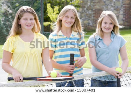 Three young girl friends with rackets on tennis court smiling - stock photo