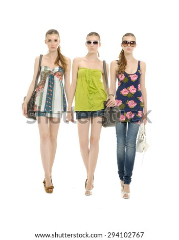 three young girl in jeans with sunglasses and with bag posing