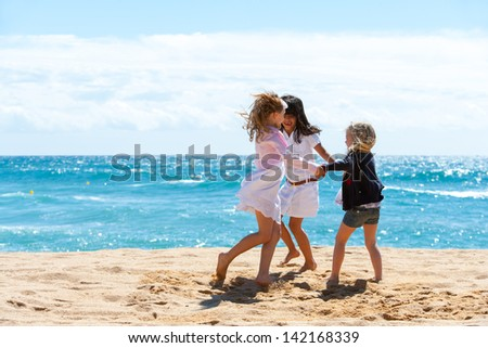 Three young girlfriends playing game on beach.