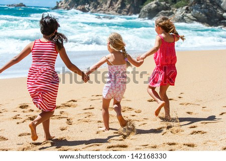Three young girlfriends running on beach holding hands. - stock photo