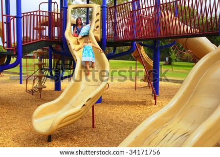 Three young girls climbing on slide at playground