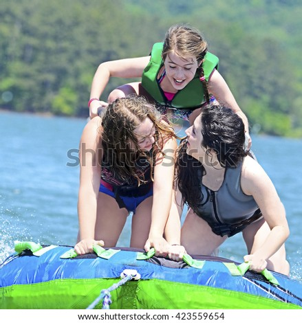 Three young girls having fun doing stunts on a tube behind a boat.