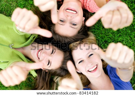 Three young girls lying down showing thumbs up sign