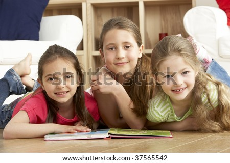 Three Young Girls Reading Book at Home - stock photo