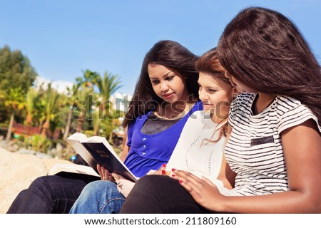 Three young girls reading together on the beach - stock photo