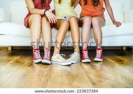 Three young girls sitting on sofa, closup on legs and sneakers - stock photo