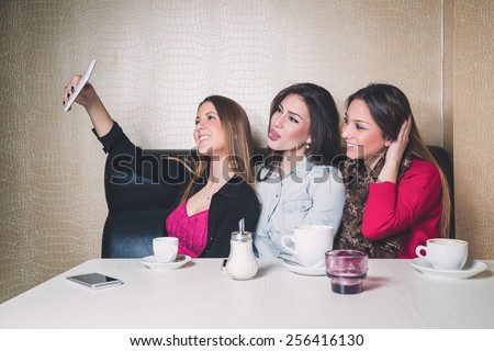 Three young girls taking selfie in a cafe - stock photo