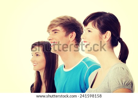 Three young happy friends. Two girls one boy smiling and looking left. - stock photo