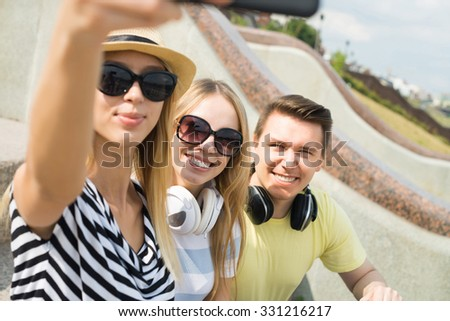 Three young happy people sitting outdoors and making selfie