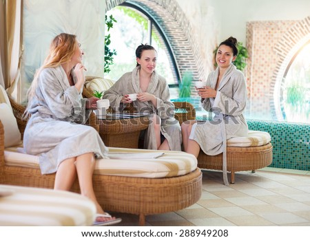 Three young happy women drinking tea at spa resort - stock photo