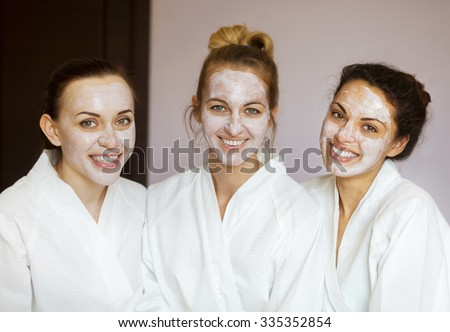 Three young happy women with face masks at spa resort. Frenship and wellbeing concept - stock photo