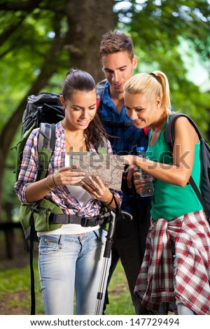 Three young hikers looking at map - stock photo