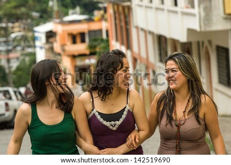 Three young Hispanic ladies sight seeing walking in the street, building in distance