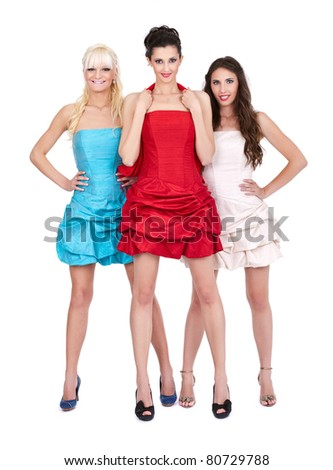 three young in fashion dresses posing on white background