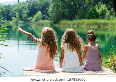 Three young kids sitting together on jetty at lakeside.  - stock photo