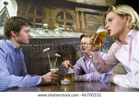 three young men drinking beer in a bar - stock photo