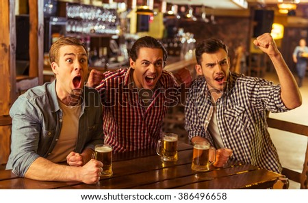 Three young men in casual clothes are cheering for football and holding glasses of beer while sitting in pub - stock photo