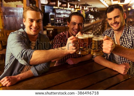 Three young men in casual clothes are smiling, looking at camera and clanging glasses of beer together while sitting in pub - stock photo