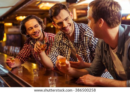 Three young men in casual clothes are talking, laughing and drinking while sitting at bar counter in pub - stock photo