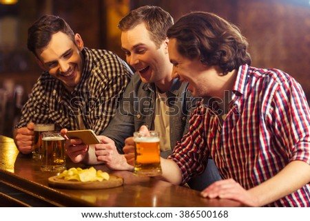 Three young men in casual clothes are talking, using a smart phone and drinking beer while sitting at bar counter in pub - stock photo