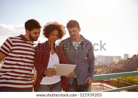 Three young millennials looking at a tablet in great concentration with very bright sunshine behind them
