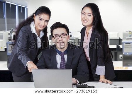Three young multi ethnic businesspeople working with laptop computer together and smiling at the camera