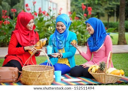 Three young Muslim girl talking at park - stock photo