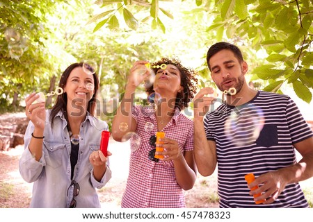 Three young people laughing and blowing bubbles in the dappled afternoon sunshine with some trees around them wearing casual clothing
