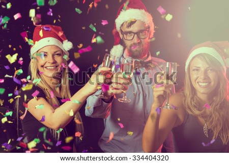 Three young people on a New Year's eve party giving a toast on midnight - stock photo