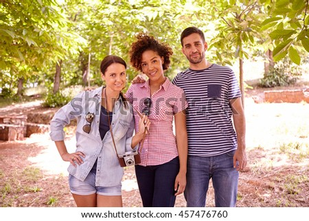 Three young people posing and smiling at the camera for a picture in the dappled shade some trees wearing casual clothing - stock photo